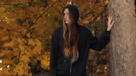 prowl : A girl coming out of the depths of the wood stops by a tree against the autumnal leaves and sunset. She holds a tree with her hand takes the hood off and looks around sullenly on the prowl. Stock Footage