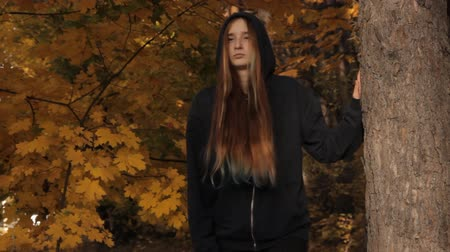 prowl : A girl coming out of the depths of the wood stops by a tree against the autumnal leaves and sunset. She holds a tree with her hand takes the hood off and looks around sullenly on the prowl. Loose hair dyed light brown, yellow, green and blue. Stock Footage