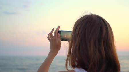 fotoğrafçı : Young woman taking pictures with smartphone on the beach Stok Video