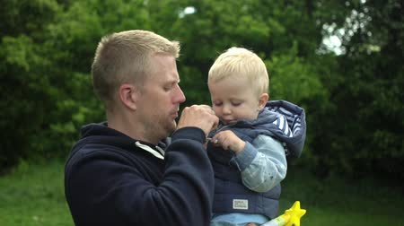 learning to walk : Portrait of happy father holds his one year old cute son in park Slow motion