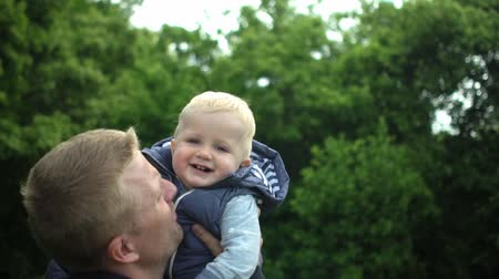 büszke : Happy father plays with one year old cute son in forest