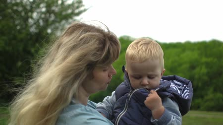 together trust : Happy young blonde mother holding and walking with her baby in park Slow motion