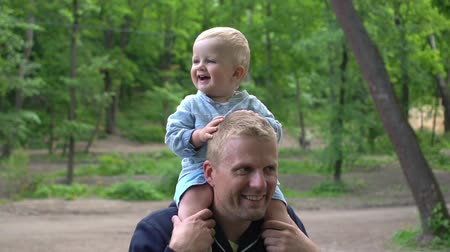 learning to walk : Happy little son on dad's shoulders in park