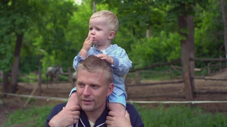 learning to walk : Happy father with son on the shoulders in park Slow motion