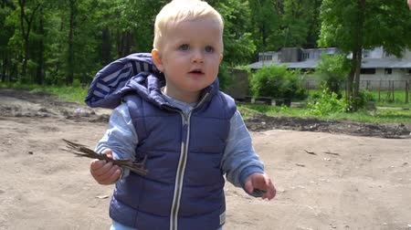 learning to walk : Happy baby boy pick up a branch from the ground in park Stock Footage