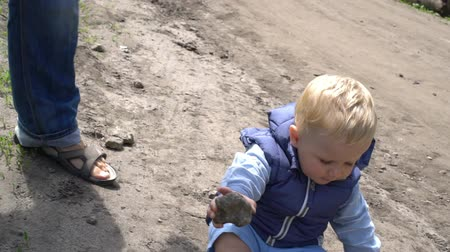 learning to walk : Happy baby boy lifting a pebble from the ground in park Stock Footage