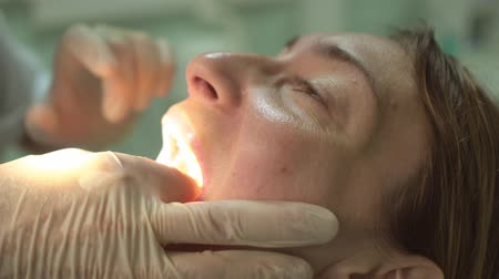 proteza : Dentist treats a tooth of female patient using dental equipment Closeup of face