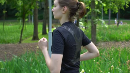 but : Young woman sprinter running in park at summertime With green grass background Slow motion