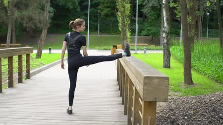 tilts : Fitness woman stretching legs before training at wood bridge. Slow motion Stock Footage