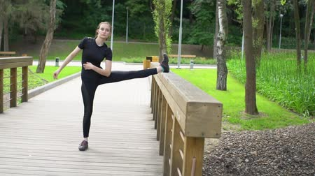 flexibilidade : Young beautiful woman stretching training on wood bridge in park at summertime. Slow motion.