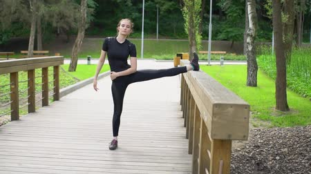 tilts : Attractive young woman stretching legs on wood bridge. Doing workout in the park. Slow motion.