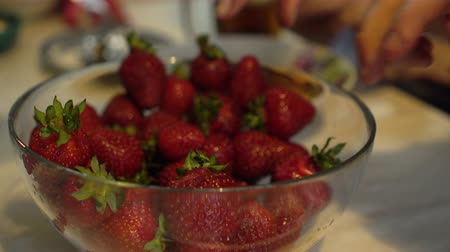 metrik : Hands try to take fresh and ripe strawberries from glass bowl
