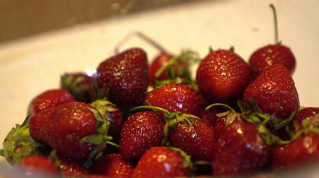 metrik : Hand takes fresh and ripe strawberries from glass bowl, put back and take another Close up Stok Video