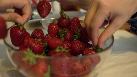 metrik : Four hands takes fresh and ripe strawberries from glass bowl Close up