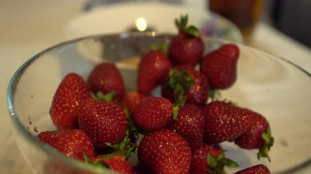 metrik : Female hands takes fresh and ripe strawberries from glass bowl Close up