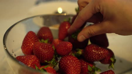 metrik : Female hands take fresh and ripe strawberries from glass bowl Close up Stok Video