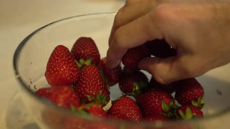 metrik : Male hand slowly take fresh and ripe strawberries from glass bowl Close up