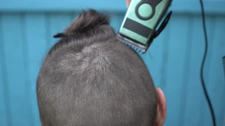 nape : Hairdresser cuts hair on nape of the client with electric razor clipper and comb Back view Close up