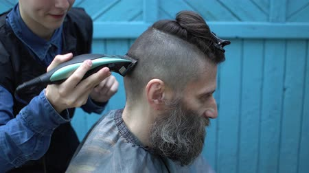 ustalık : Woman hairdresser shearing gray beard of middle-aged man with hair electric razor and comb in outdoor hairdressing salon Stok Video