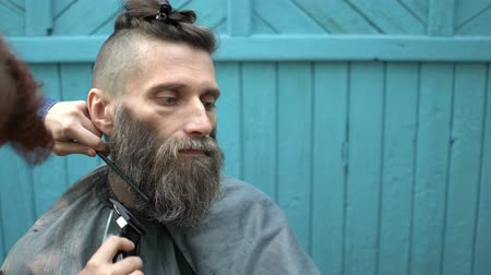 trim : Beard styling with electric trimmer. Barber hand cutting beard with clipper and comb at outdoor barbershop Stock Footage