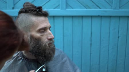 ustalık : Beautiful barber woman carefully trimming beard of client with clipper and comb at outdoor barbershop