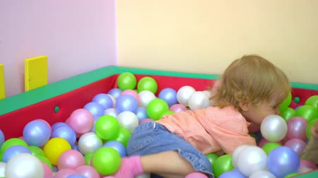 socializing : Happy caucasian toddlers having fun and playing in multi coloured ball pool. Preschool