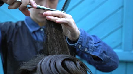 trim : Closeup of woman hairdresser cutting hair of strange middle-aged hipster man in experimental outdoor barbershop on summer festival of hairstyles Stock Footage