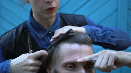trim : Young hairdresser slowly combing and cutting hair of strange middle-aged hipster man in experimental outdoor barbershop on summer festival of hairstyles. Man looks into smartphone as mirror and gives directions to hairdresse Stock Footage
