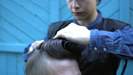 мастер : Woman hairdresser slowly combing and cutting hair of strange middle-aged hipster man in experimental outdoor barbershop on summer festival of hairstyles. Man looks into smartphone as mirror and gives directions to barber Стоковые видеозаписи