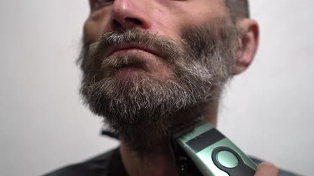 shaver : Attractive man shaves his beard with electric shaver Stock Footage