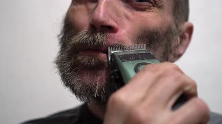 shaver : Bearded man dry shaving beard using electric trimmer machine