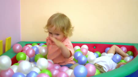 socializing : Happy toddlers laughing and playing in multi coloured ball pool. Preschool Stock Footage
