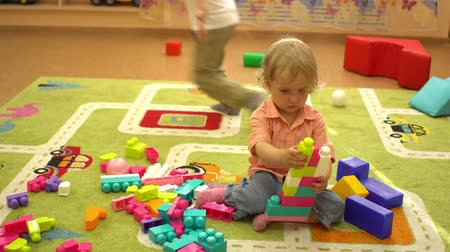 socializing : Happy preschool children playing with multi coloured blocks at indoor playground. Child sport activity