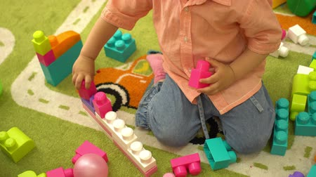pré escolar : Preschool little girl playing with multi coloured building blocks in kindergarten. Child development in nursery school Stock Footage