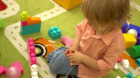 construtor : Preschool baby girl playing with multi coloured building blocks in kindergarten. Child development in nursery school