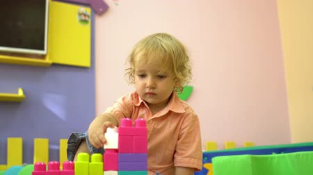 construtor : Beautiful blonde preschool toddler playing with multi coloured building blocks in kindergarten. Child development in nursery school Stock Footage