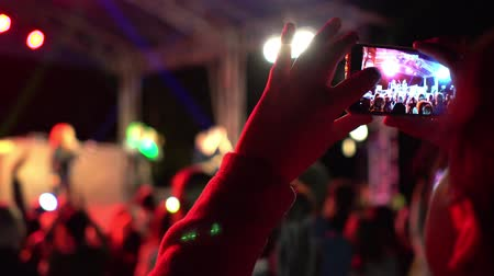 Hands of girl making video of summer festival concert with mobile phone. Crowd celebrating party event. Defocused image. Concept of fun, music and entertainment. Original multi colored lights blurred background