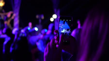 Young woman holding smartphone in hands, shooting vide and looking at digital display. Crowd partying at live open air rock concert. Multicolored blurred background from stage