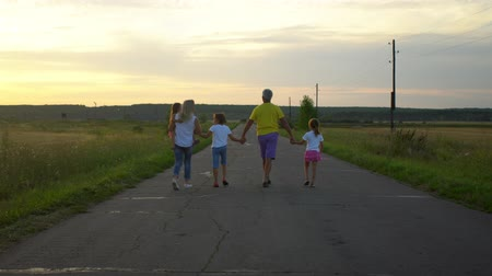 Mature parents with three children go along road in countryside. Happy family have fun on nature. Travel, tourism, hike and people concept
