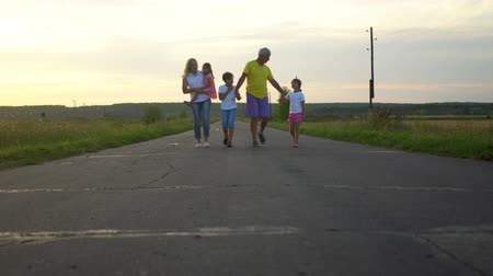 Happy family go along road in countryside. Mature parents with three children have fun on nature. Family, parenthood, adoption and people concept Wideo