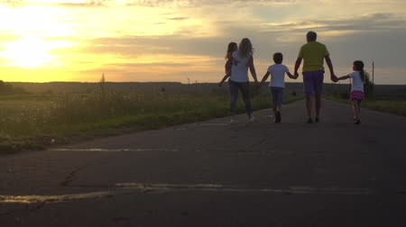 Mature parents with three children go on road in countryside on sunset. Happy family have fun on nature. Travel, tourism, hike and people concept
