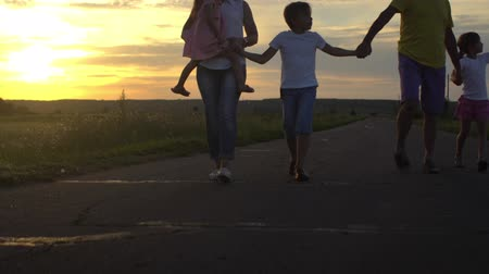 Happy father and mother with three children go on road in countryside on sunset. Happy family have fun on nature. Travel, tourism, hike and people concept 動画素材