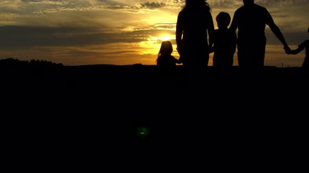 Silhouettes of happy family walking in meadow at sunset in countryside. Travel, tourism, hike and people concept Wideo