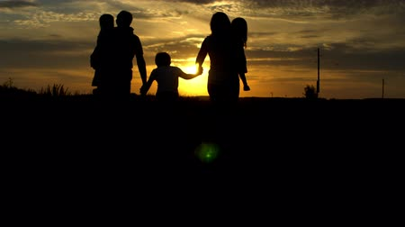 Silhouette of happy family going to sunset