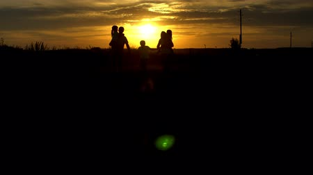 Silhouettes of happy family walking at sunset in countryside. Travel, tourism, hike and people concept Summertime Wideo