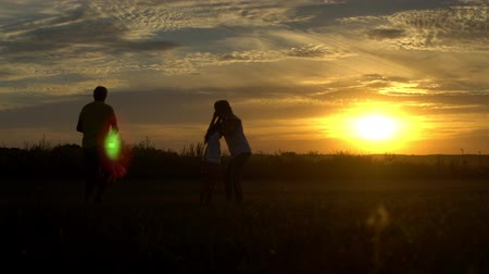 Silhouette of parents playing with children at sunset in countryside. Travel, tourism, hike and people concept Summertime