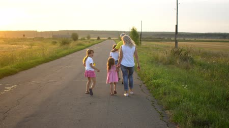 five : Happy mature father and mother with three children go on road in countryside on sunset. Happy family have fun on nature. Travel, tourism, hike and people concept Summertime