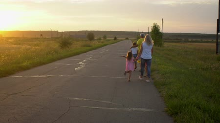 Happy mature father and mother with three kids go on road in countryside on sunset. Happy family have fun on nature. Travel, tourism, hike and people concept Summertime Wideo