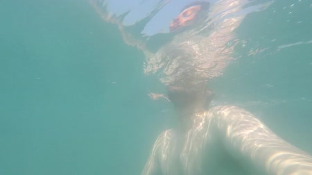 Underwater view of young man swimming in the ocean POV Vacation Summertime