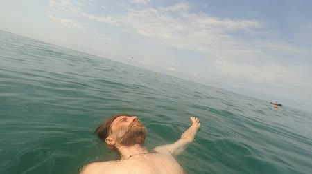 POV of man with beard swimming and in sea water on sunny day with action camera Summertime